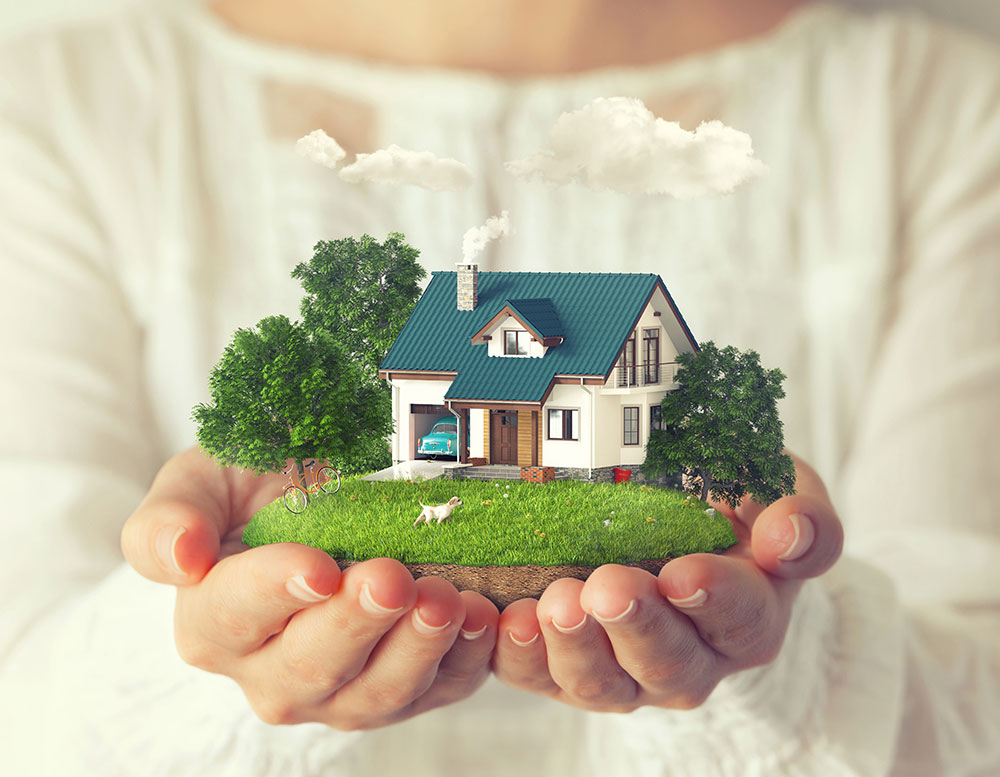 a tiny house with a green lawn and trees in a woman's hands
